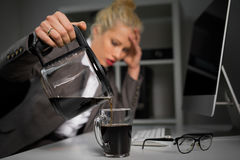 Woman pouring coffee in cup. Tired woman pouring coffee in cup stock photos