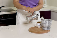 Woman pouring coffee from a percolator Stock Images