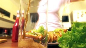 Woman pouring cola drink into glass near plate with hotdogs stock video footage