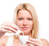 Woman pouring cream or milk into cup of coffee Royalty Free Stock Photos