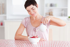Woman pouring cream over strawberries Stock Photography