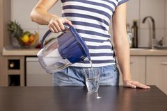 Free Woman Pouring Filtered Water Into A Glass Stock Photos - 137873603