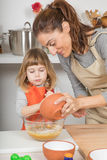 Woman pouring flour in bowl and child beating Royalty Free Stock Photos