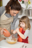 Woman pouring flour in bowl and child whipping Stock Photo