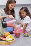Woman pouring fruit from a blender Stock Photos