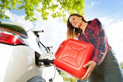 Woman pouring fuel into gas tank of a car from can. Low-angle shot of beautiful young woman pouring fuel into the gas tank of her car from a red can royalty free stock photos