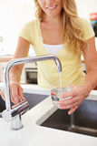 Woman Pouring Glass Of Water From Tap In Kitchen. Close Up Of Woman Pouring Glass Of Water From Tap In Kitchen stock photography
