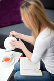 Woman pouring herself a cup of tea Stock Images