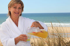 Woman pouring herself juice Stock Photo