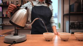 Woman pouring hot water into a bowl with grind coffee during coffee food function at the coffee shop.