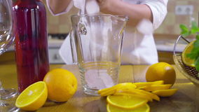 Woman pouring ice into a pitcher slow motion stock video