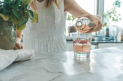 Woman pouring kombucha in the kitchen royalty free stock photography