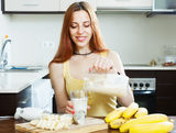 Woman  pouring milk shake with bananas Royalty Free Stock Photo