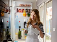 Woman pouring milk while standing near from the refrigerator Stock Image