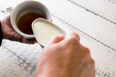 Woman pouring milk in to the cup of coffee to make a morning espresso. Breakfast and home equipment concept. Stock Image