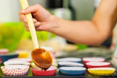Woman pouring muffin dough in paper case royalty free stock photo