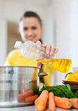 Woman pouring oil from bottle into the saucepan Royalty Free Stock Image