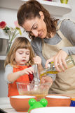 Woman pouring oil in bowl and child whipping Royalty Free Stock Photo