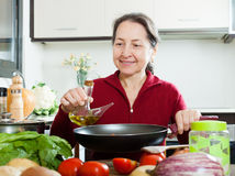 Woman pouring oil into girdle Stock Image