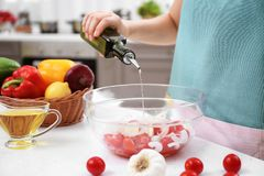 Woman pouring olive oil onto vegetable salad Royalty Free Stock Photos