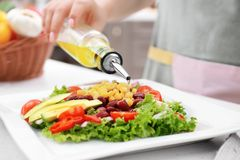 Woman pouring olive oil onto vegetable salad Stock Photography