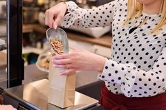 Woman pouring pinto bean to paper paper bag. In a shop Stock Photo