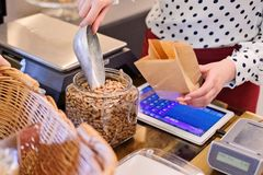 Woman pouring pinto bean to paper paper bag. In a shop Royalty Free Stock Photos