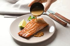 Woman pouring sauce onto tasty cooked salmon. On plate, closeup Royalty Free Stock Photo