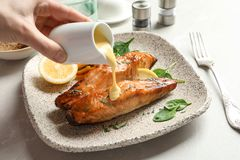 Woman pouring sauce onto tasty cooked salmon. On plate, closeup Royalty Free Stock Image