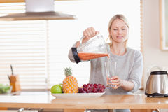 Woman pouring self made juice into a glass Royalty Free Stock Photography