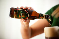 Woman Pouring Smithwick's Beer Into Cold Mug Stock Photo