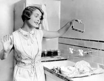 Woman pouring soap on dishes Royalty Free Stock Photo