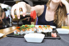 Woman pouring soya sauce in a bowl. Pour soya sauce in a white small bowl for sushi Royalty Free Stock Image