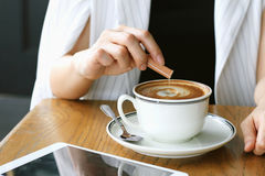 Woman pouring sugar into coffee cup. Sugar addicted concept stock image