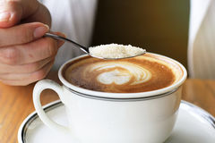 Woman pouring sugar into coffee cup. Sugar addicted concept royalty free stock image