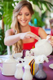 Woman pouring tea in the cup Royalty Free Stock Photos