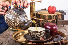 Woman pouring tea from teapot on vintage wooden table Stock Photo