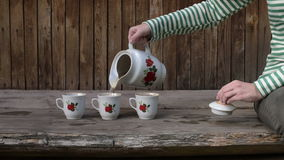 Woman pouring tea into three mugs stock video footage