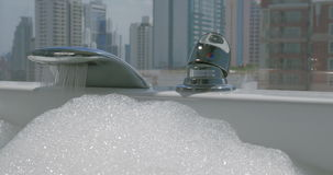 Woman pouring water into the bathtub with foam. Close-up shot of woman turning on the faucet and water pouring into the bath with foam. Bathtub at the panoramic stock footage