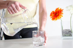 Woman pouring water into a glass Stock Photos