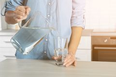 Woman pouring water into glass at table