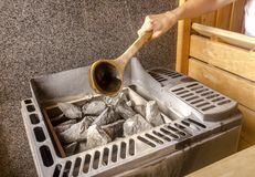 Woman is pouring water into hot stone in Sauna spa room.  Stock Photo
