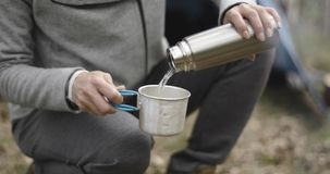Woman pouring water from thermos bottle to camping glass. Couple people in love autumn outdoor trip in nature. Fall. Sunny day. 4k slow motion video stock footage