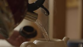 Woman pours boiling water into the cup and brew tea in a tea bag. The woman pours hot water into the teapot with tea stock video