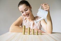 Woman pours coins Stock Photo