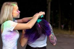 Woman pours dry paint on hair to her friend on Holi festival. Woman pours dry color paint on hair to her friend on Holi festival stock images