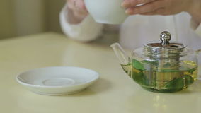 Woman pours green tea from teapot stock video