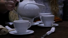 Woman pours herbal tea in a white cup in cafee. slow motion. Woman pours herbal tea in a white mug in cafee. slow motion stock video footage