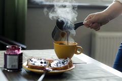 Woman pours hot coffee from cezve in  mug Royalty Free Stock Images