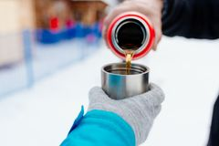 Woman pours hot tea or coffee from metal thermos Stock Photo